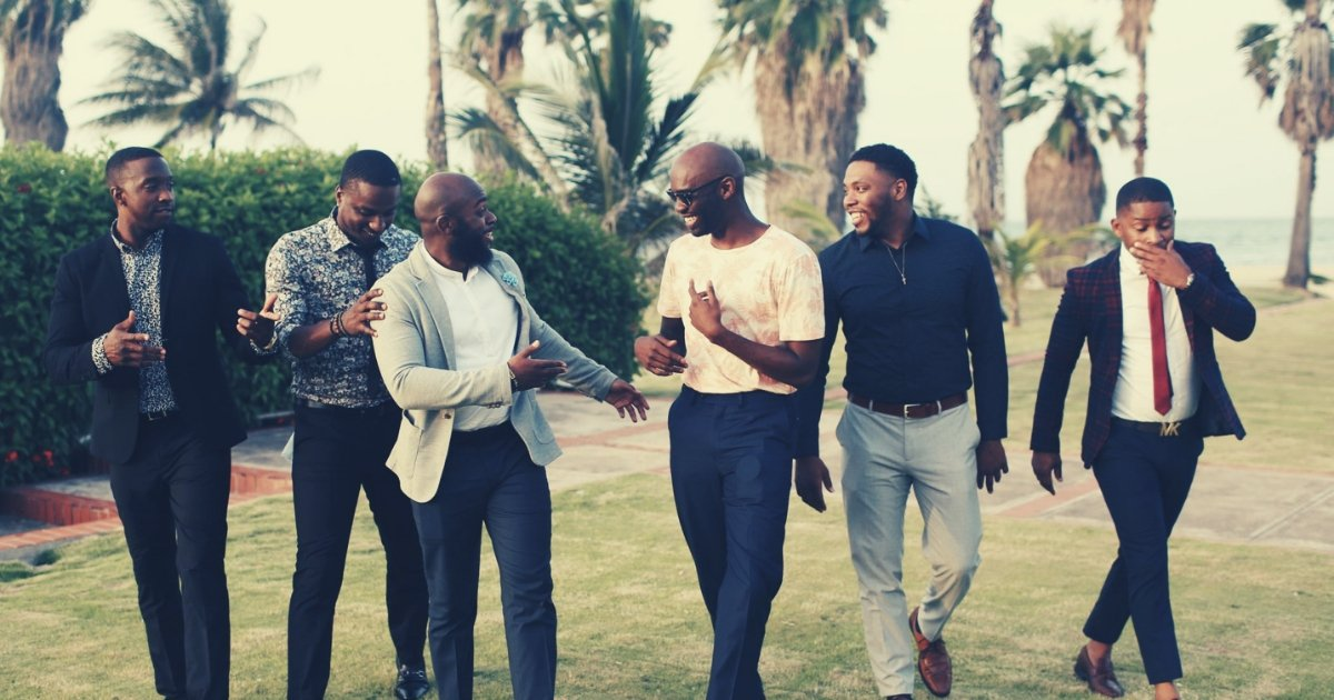 five african american men strolling and laughing in a garden