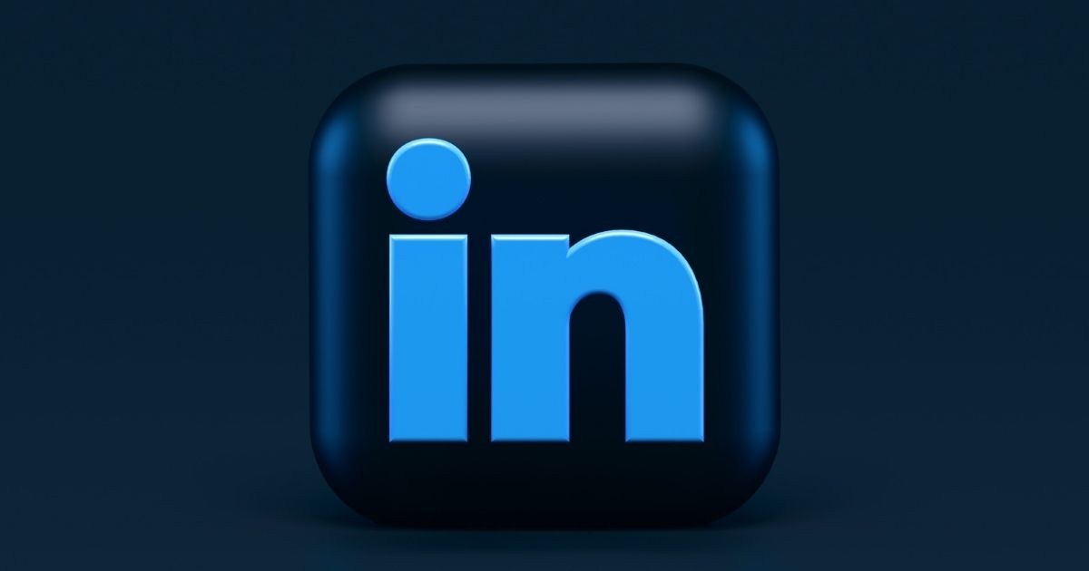 Blue LinkedIn icon displayed on a black cube on a black background