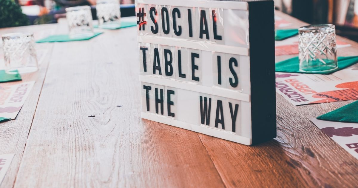 White and Black Signage on a Wooden Table