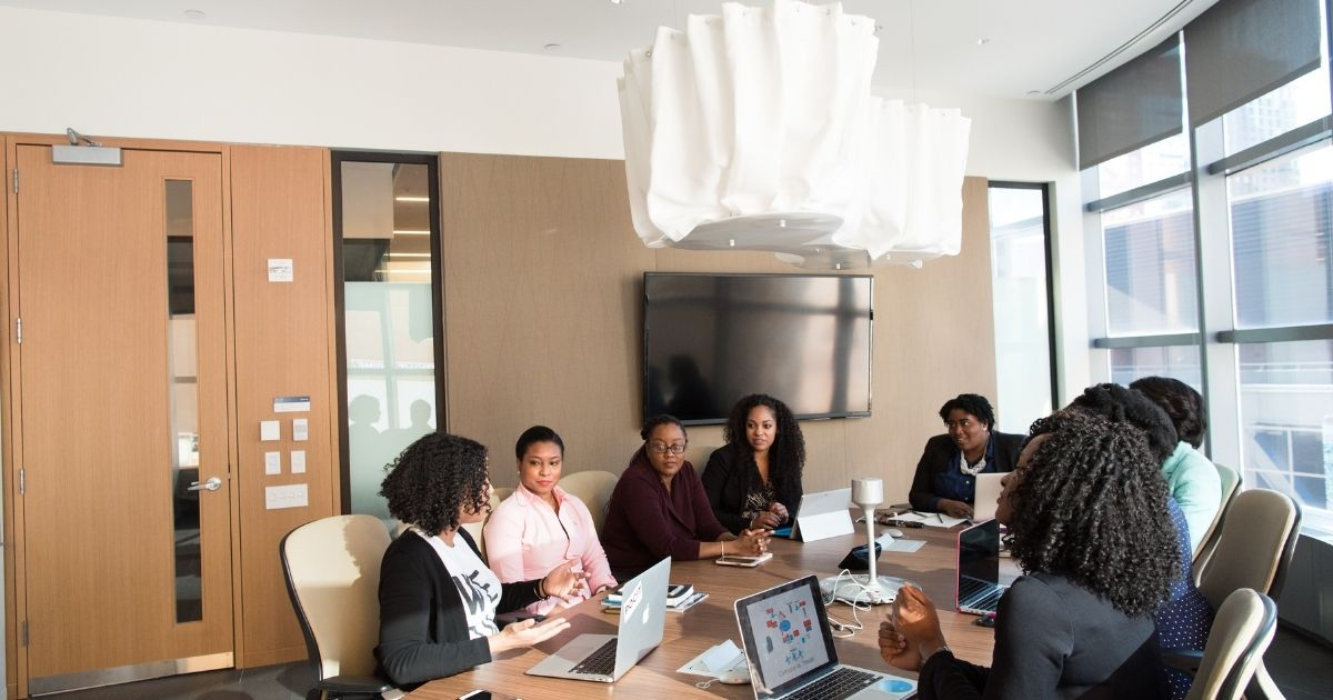 A group of women sitting around a conference table with their laptop computers