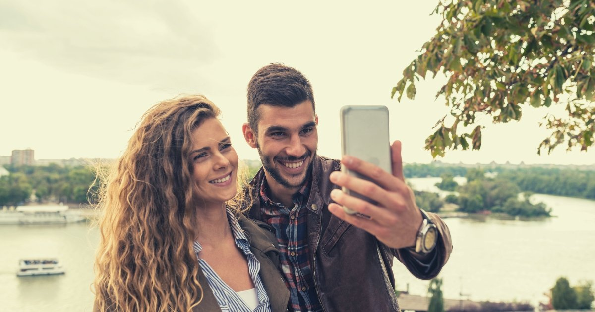 man and woman with smartphone taking selfie