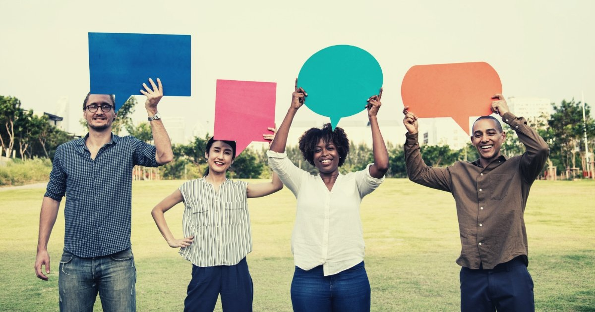 four persons holding up large coloured speech bubbles in a green field